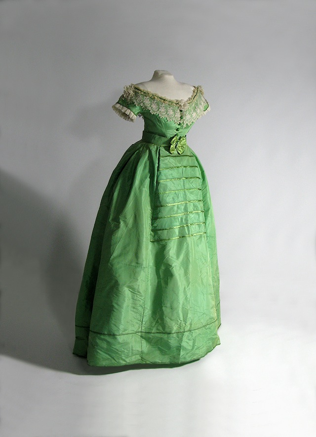 """English or French, c. 1860–1865. This dress came with both a low‐cut bodice for evening wear and a more buttoned‐up bodice for daytime wear. Many Victorian dresses, including this one, were made with both styles of top and the advantage of """"Emerald Green"""" was that it kept its bright colour in both natural and gas lighting. Collection of Glennis Murphy. Photo credit: Image © 2014 Bata Shoe Museum, Toronto, Canada (photo: Arnold Matthews)"""