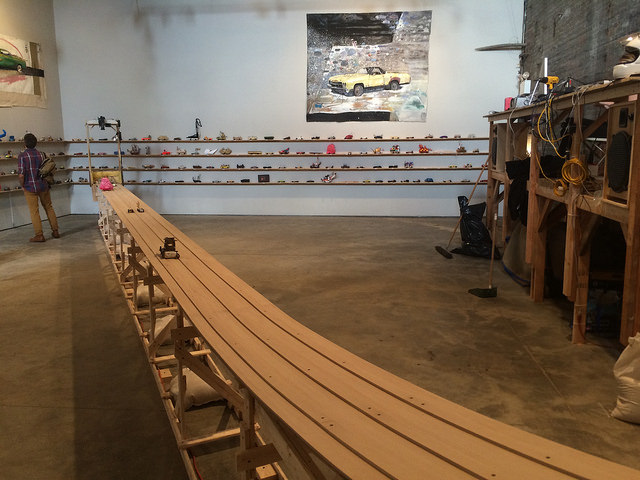 A view of Peirogi Boiler with all the gravity racers lined up against the wall and the track in the middle. (all photos by the author for Hyperallergic)