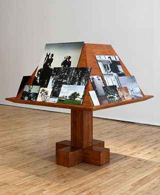 "Jill Magid, ""Der Trog"" (2013), from her installation Facistol (pine lectern inspired by Luis Barragán, mounted reproductions from Luis Barragán's personal archive), architectural model, as it was exhibited at Art in General during Performa 13. (photo by Steven Probert, via artingeneral.org)"