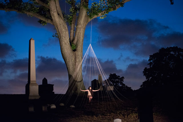 """A performer in """"Crossing Over: A Performance Adventure in Green-Wood Cemetery"""" (all photos by Monica Simoes, lighting design: Mike Faba)"""
