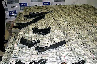 Drug money and weapons seized by the DEA in 2007 (image via Wikimedia)