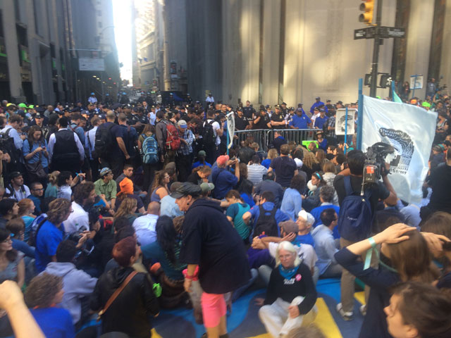 Protesters sitting at the corner of Broadway and Wall St. (photo by Hrag Vartanian/Hyperallergic)