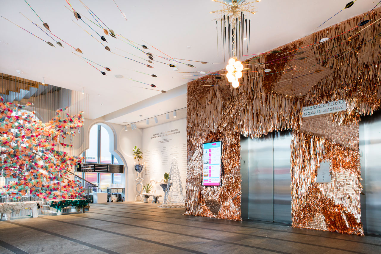 """Installation view, 'NYC Makers: The MAD Biennial' at the Museum of Arts and Design, 2014, including detail of """"Fringe Wall–Copper"""" (2014) and """"Catalogue"""" 01 (2014) by CONFETTISYSTEM; two iterations of Pig Bench (2014), Heyerdahl Bench, and Heyerdahl Coat Rack/Planter/Lamp, (2014) all by Misha Kahn; """"100 Arrows"""" (2014) by Fredericks & Mae; """"Totem"""" II (2014) by Lindsey Adelman with Nancy Callan; and """"X-Tower"""" 54.4 (2013) by MILGO/BUFKIN , fabricator and Haresh Lalvani, designer (photo by Eric Scott)"""