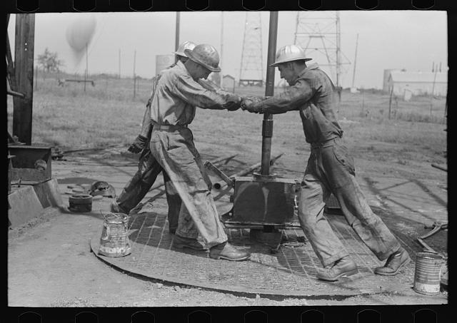 Roughnecks tighening a pipe on an oil well, Oklahoma City, photograph by Russell Lee (August 1939) (via Photogrammar/Library of Congress)