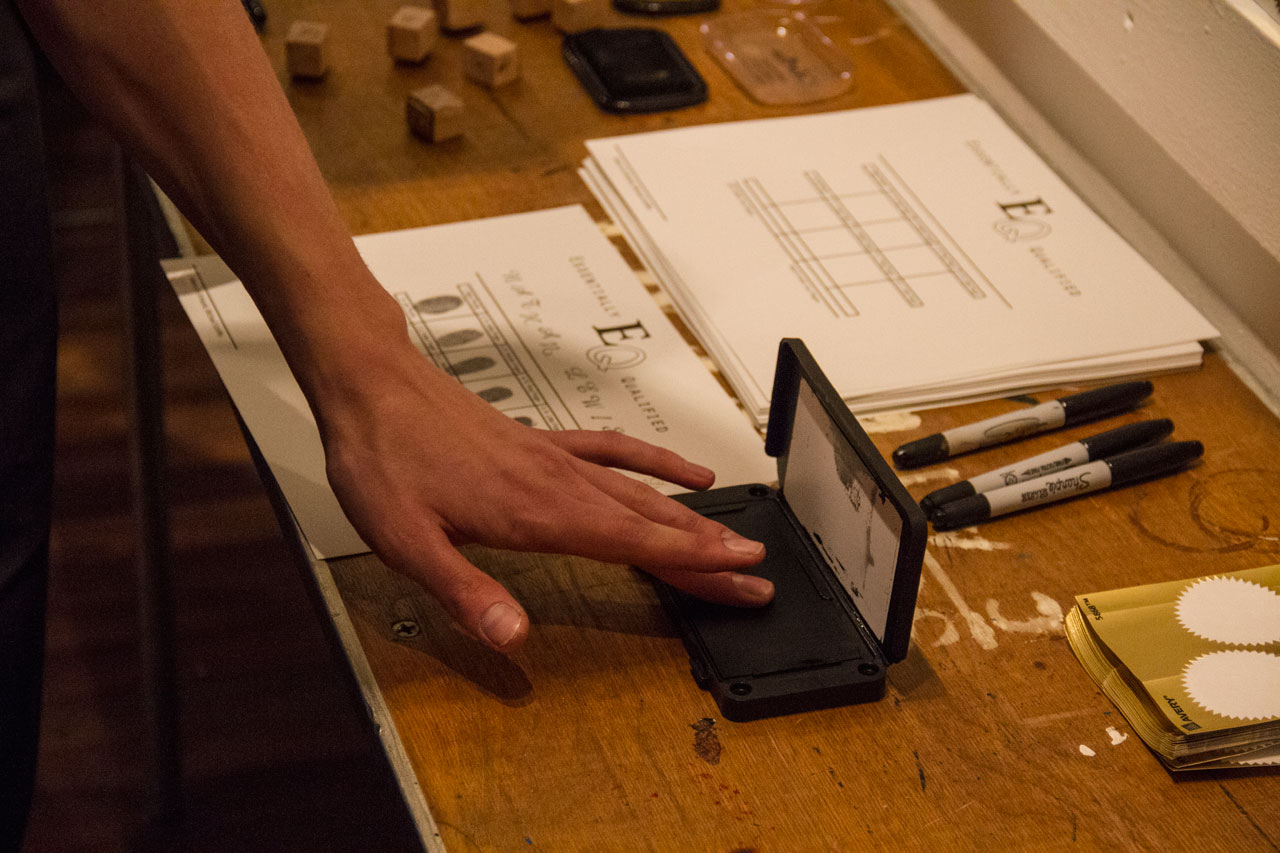 """Participant creating a hands-on diploma at Paul Shortt's """"Diploma Station"""" (2014), stamps, seals, and certificates"""