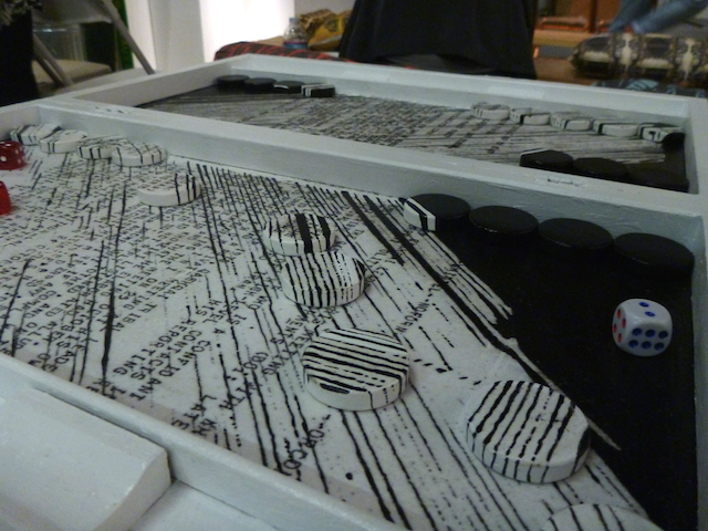 """According to the artist statement, Gelare Khoshgozaran's Convergences is a backgammon board whose background contains pieces of """"archives from the US Iran-Contra documents collected and restructured after the occupation of the US Embassy by the Iranian Revolutionary Students in 1980 Tehran."""" The checkers start camouflaged in the board and over time, the messages are distorted and shifted as the game commences."""