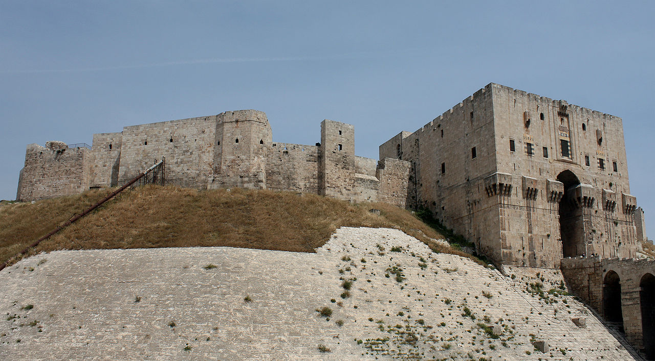 The Citadel of Aleppo, one of many sites damaged by the Syrian Civil War (Image via Wikimedia)
