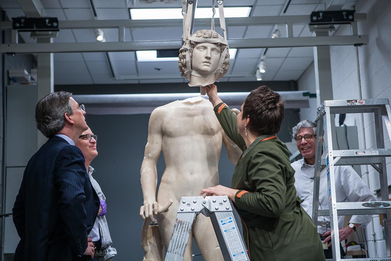 Conservators prepare to reattach Adam's head.