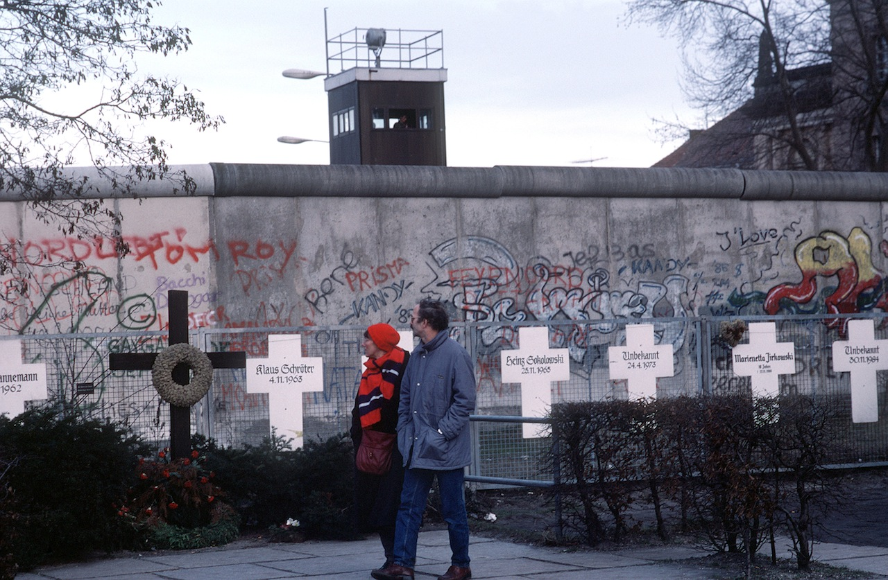 The White Crosses memorial on a fence in front of the Berlin Wall, where they were first installed in 1971. (Image via Wikimedia)