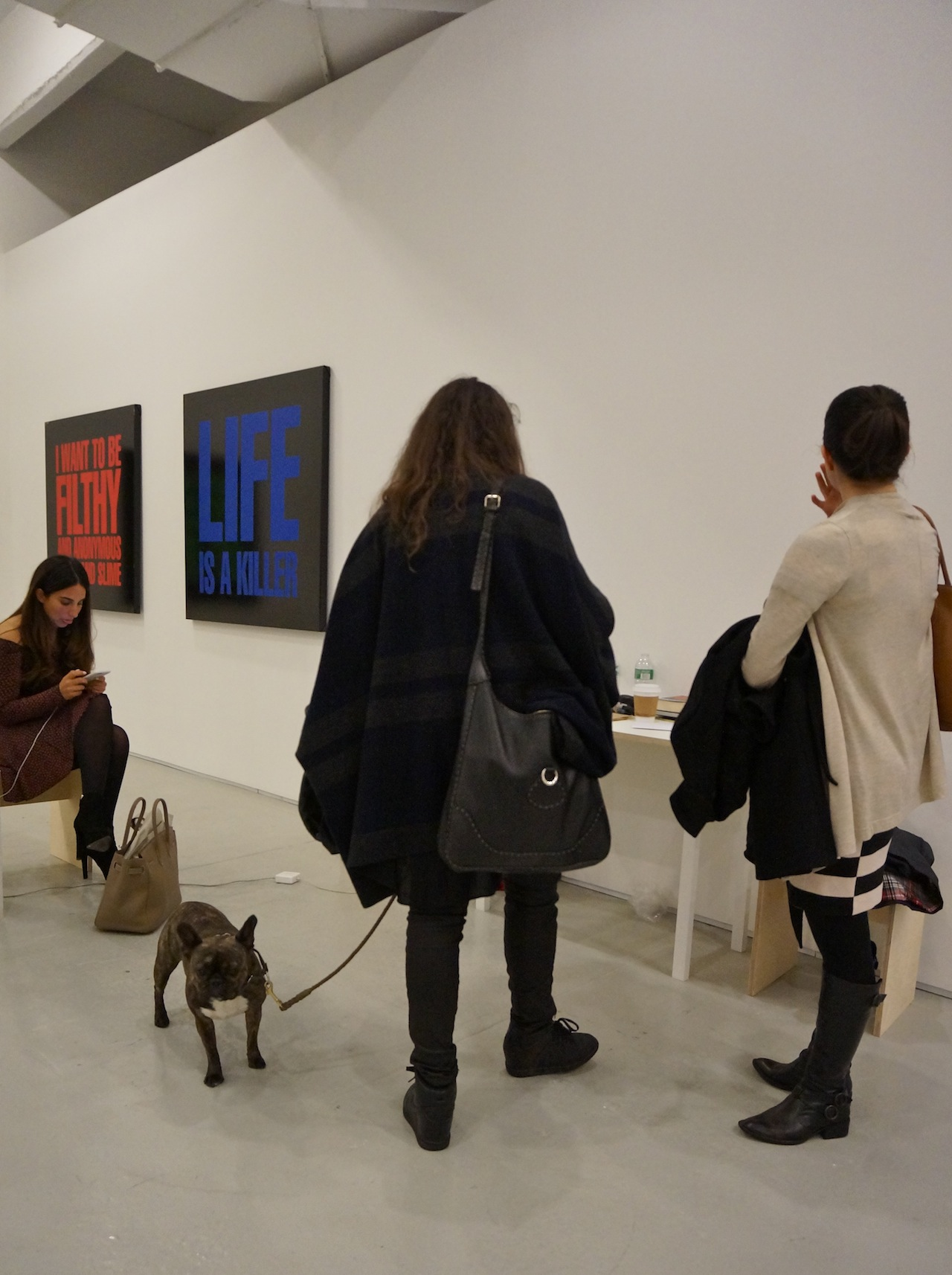 Women and dog visit the booth of Max Wigram Gallery, showing 1989 paintings by John Giorno