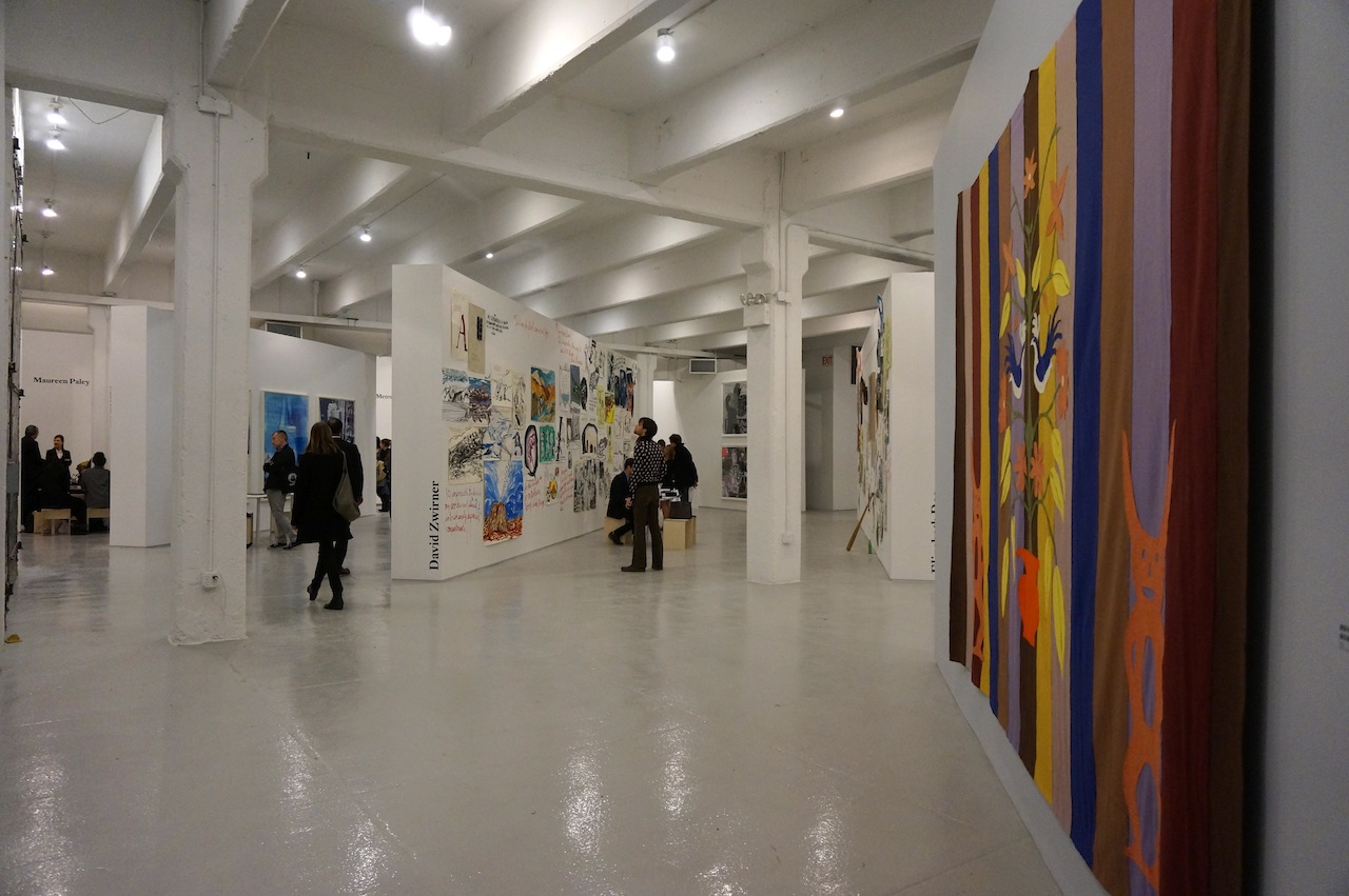 A view of Independent Projects, with a felt banner by Mike Kelley on the right and David Zwirner's booth of Raymond Pettibon in the center back