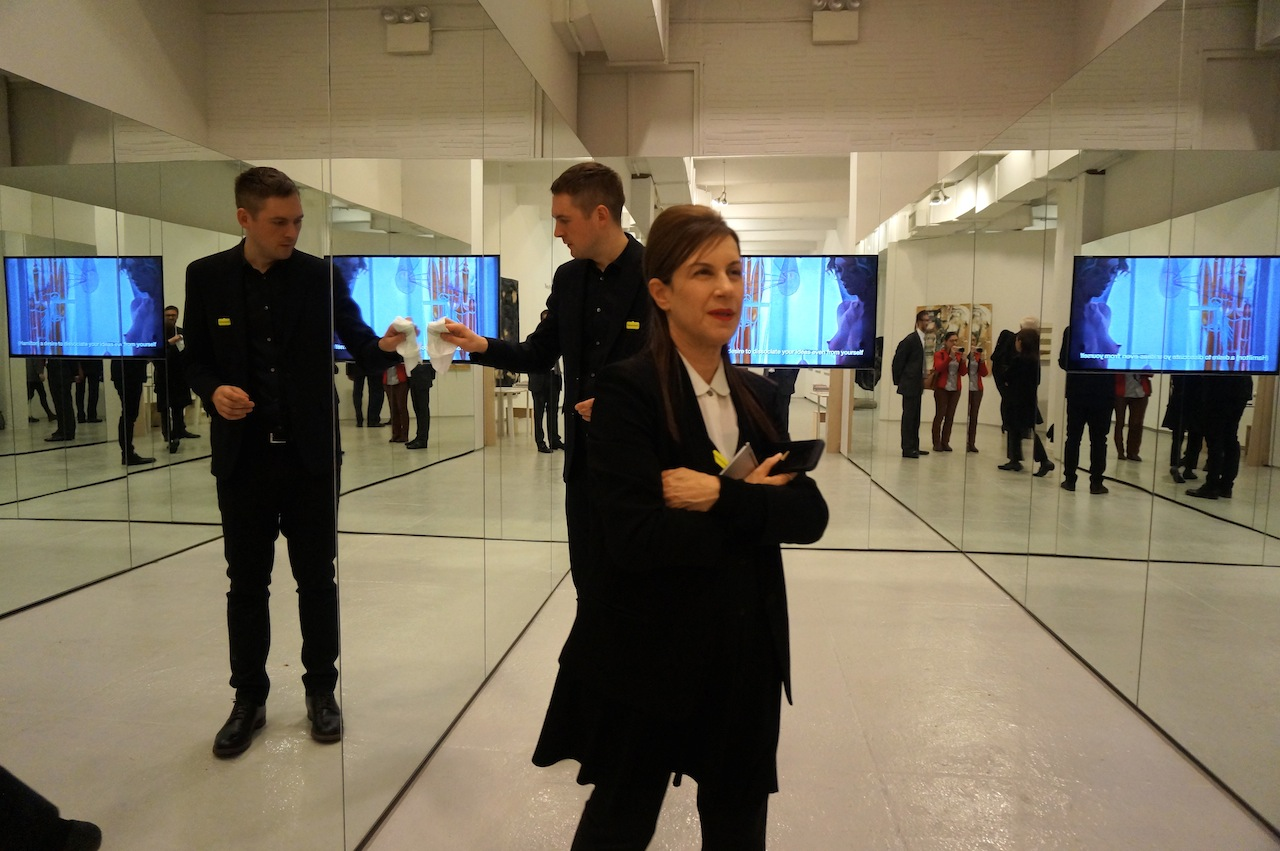 """Cleaning Liam Gillick's mirrored room, which houses his film """"Hamilton: A Film by Liam Gillick"""" (2014), at Marueen Paley"""