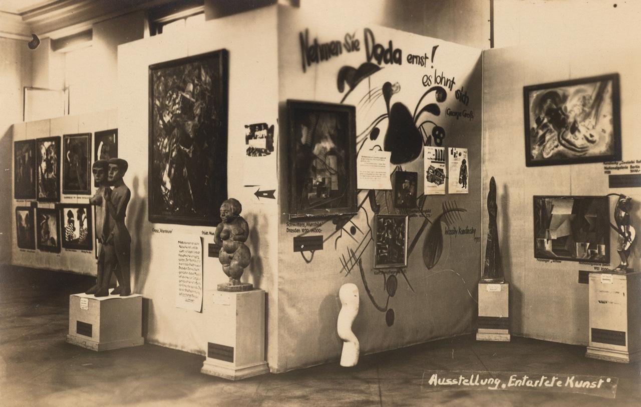 "'Entarte Kunst' Berlin exhibition postcard, showing artworks and signage ""Nehmen sie Dada Ernst"""