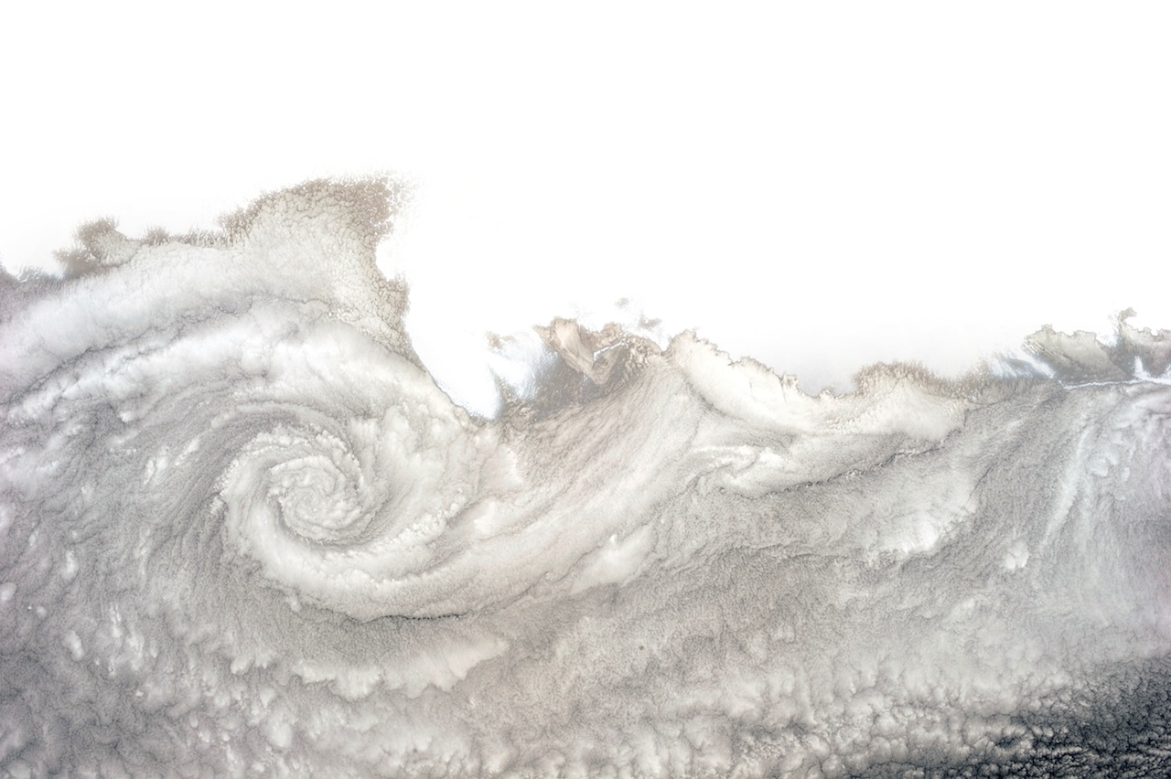 """A cloud twist over Arica, Chile. Hadfield writes: """"You see these frequently in this part of the world because the Pacific is cold, the land is warm, and the currents and winds combine to form a cloudy vortex—clockwise here, because it's the southern hemisphere. North of the equator, the spiral would turn counter-clockwise.""""  (photograph by Chris Hadfield/NASA)"""