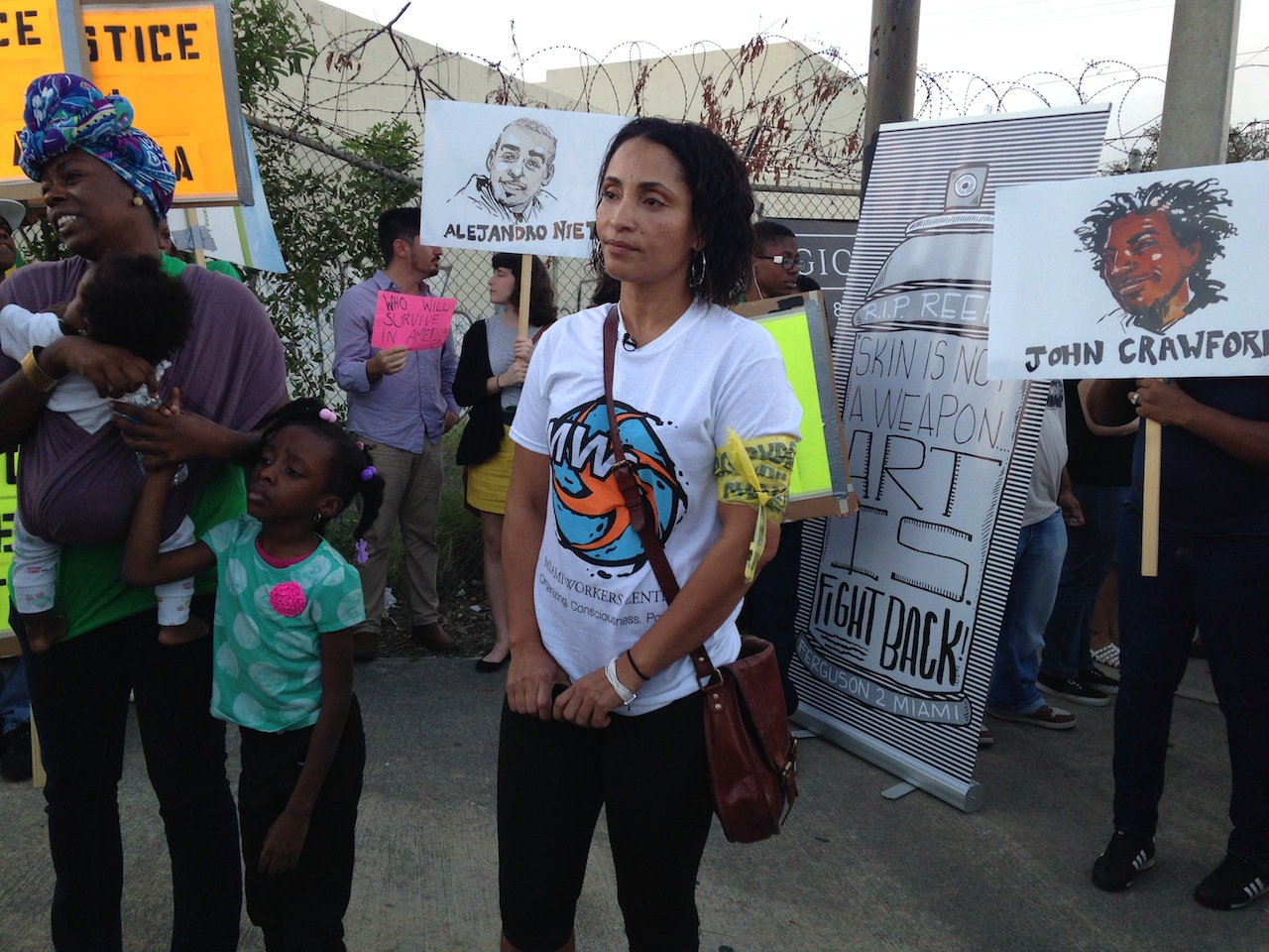 At the protest, with Ruth Noel Jean standing on the far left and protest art by Molly Crabapple and Damon Davis in the background