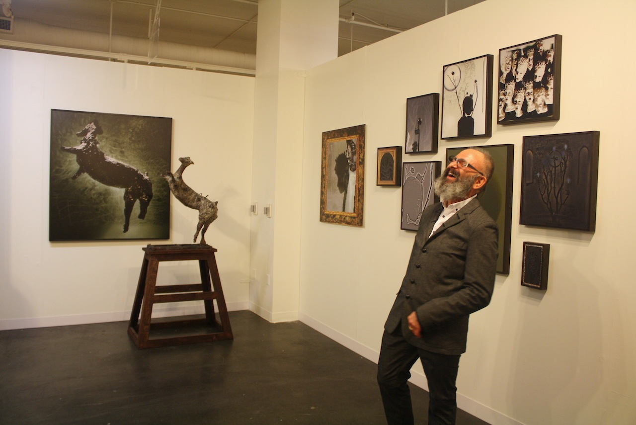 Simon Toparovsky, caught mid-laugh in front of his work.