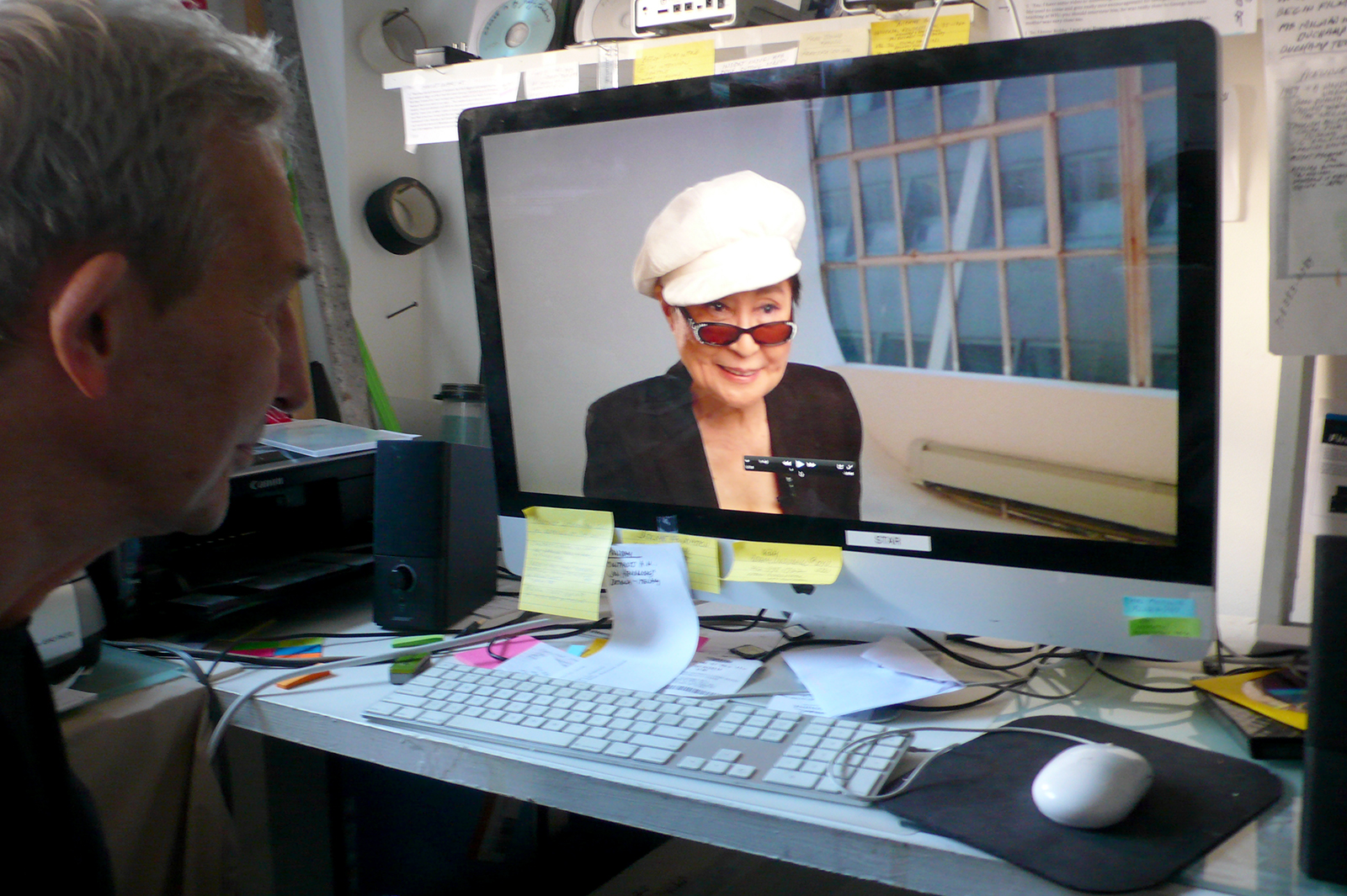 Jeffrey Perkins watches artist Yoko Ono in her interview for his film about George Maciunas (photo by Edward M. Gómez for Hyperallergic)