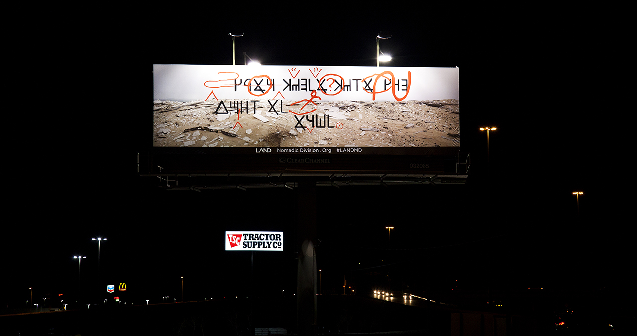Billboard #1 at night above interstate highway (Image courtesy of the artist)