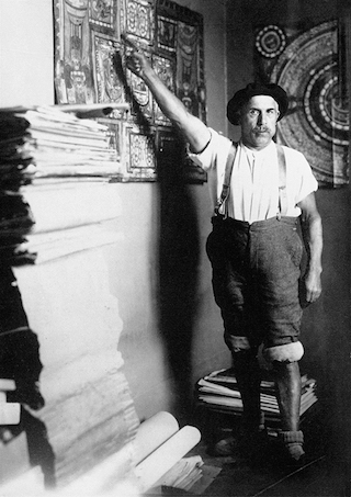 Adolf Wölfli in his room at the Waldau Psychiatric Clinic near Bern, Switzerland, in 1921, with a stack of his handmade, illustrated books (© Adolf Wölfli Foundation, Kunstmuseum Bern)