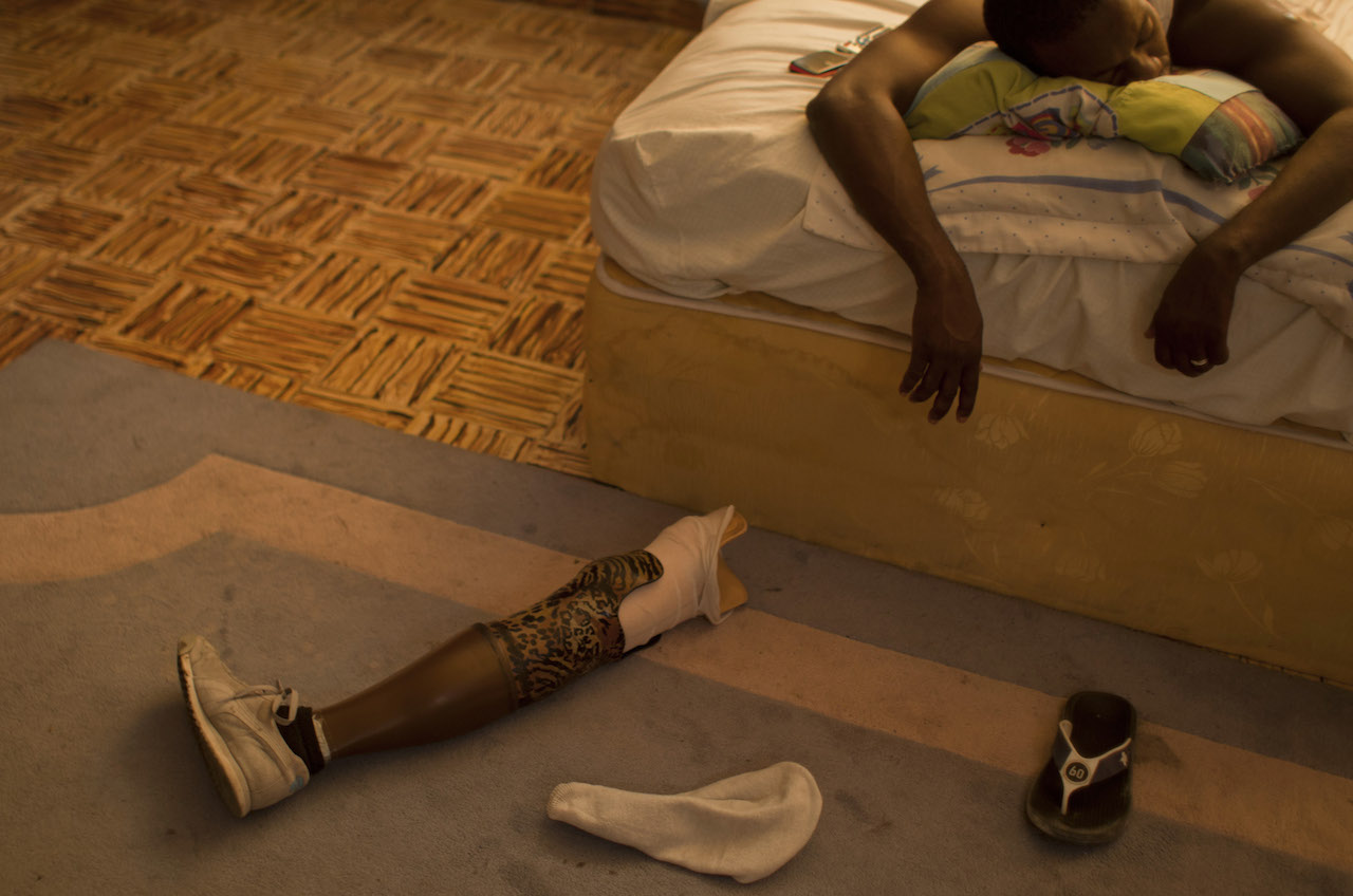 Georges Exantus. In this Jan. 17, 2013 photo, professional dancer Georges Exantus sleeps as his prosthetic limb lays on the floor in his bedroom in Port-au-Prince, Haiti. Exantus thought he'd never dance again. He was lucky just to be alive. The earthquake three years ago in Haiti's capital flattened the apartment where he was living, where he spent three days trapped under a heap of jagged rubble. After friends dug him out, doctors amputated his right leg just below the knee. Exantus says he has learned to ignore the long stares and quiet whispers, products of a longstanding stigma in Haiti for people with disabilities. Before the quake, few resources existed to accommodate Haiti's disabled, and many regard people with disabilities as misfits. © Dieu Nalio Chery/ AP Photo.