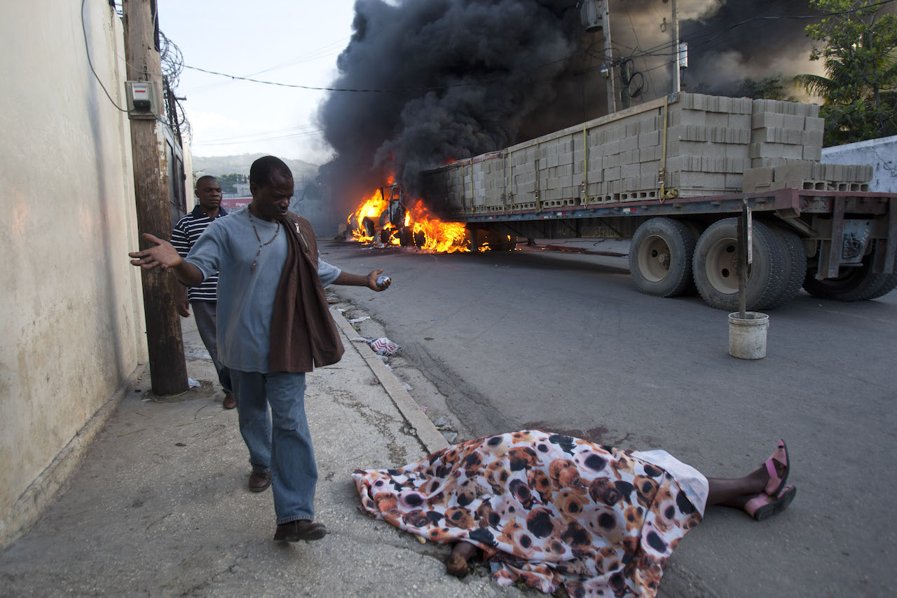 Dasilia Daniel. A resident expressing shock, walks by the body of rice vendor Dasilia Daniel, who was accidentally shot dead during a road rage incident as she walked to work in the Petionville surburb of Port-au-Prince, Haiti, Friday, July 19, 2013. According to Daniel's cousin, Aclite Laurent, the driver of a semi-trailer truck, pictured in background, tapped the back of a pickup, enraging its driver, who then stepped out from his vehicle, gun in hand, and shot at the semi-truck driver, missing him and killing Daniels. Fellow vendors set the vehicles on fire in retaliation for the death of their friend. © Dieu Nalio Chery/ AP Photo.