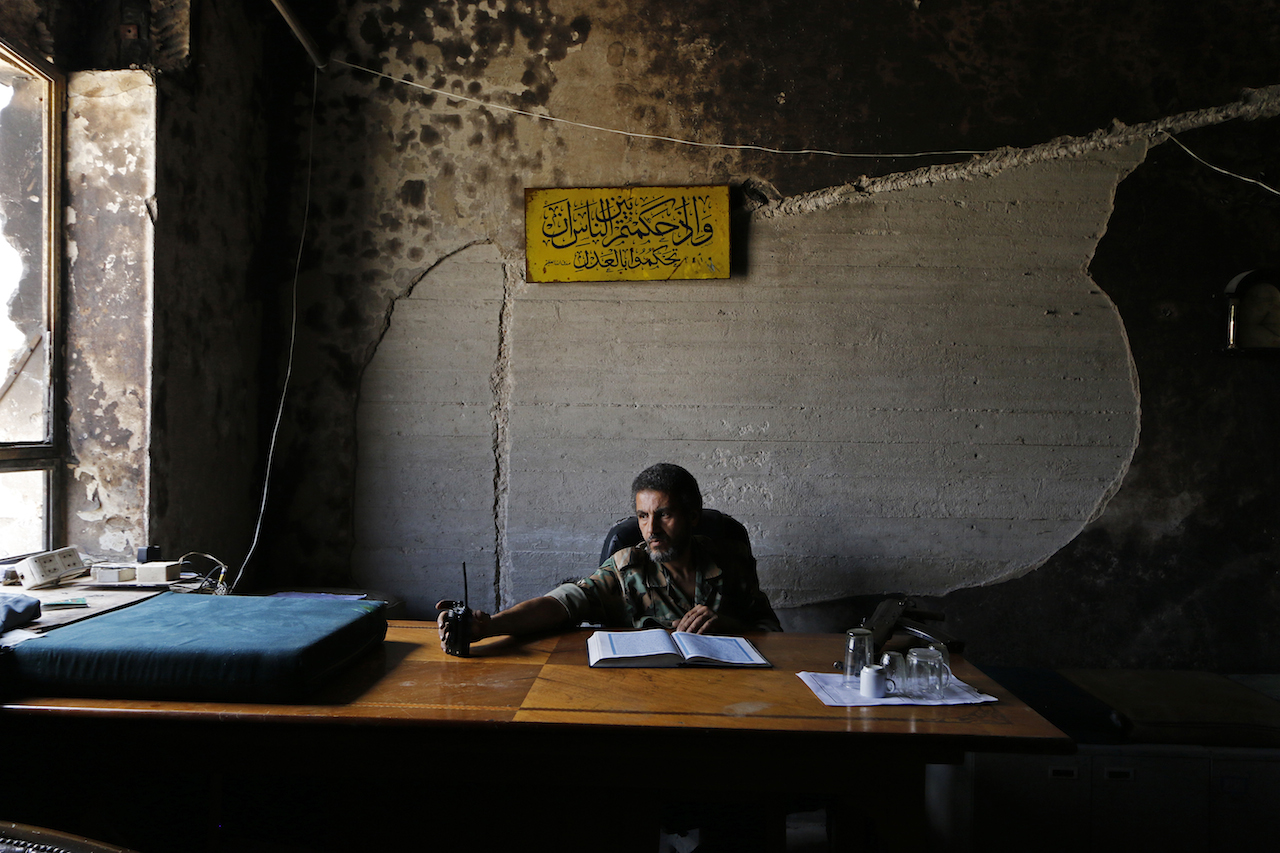 A Free Syrian Army fighter sits behind a desk in Palace of Justice in Aleppo, June 6, 2014. © Nour Kelze.