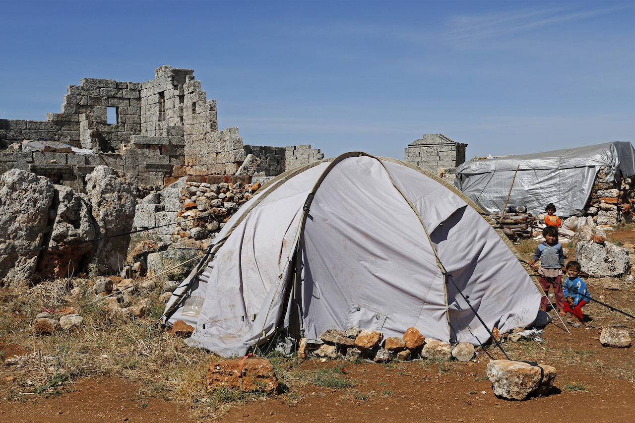 Children, who have been displaced due to the fighting between rebels and the forces of Syrian President Bashar al-Assad, sit beside a tent at the Shinshrah archaeological site, in the Idlib countryside. Many Syrians living close to the frontline fled to live at the Shinshrah archaeological site about two years ago, activists said. The site now contains a school, a mosque and recently the community was digging a water well. May 18, 2014. © Nour Kelze.