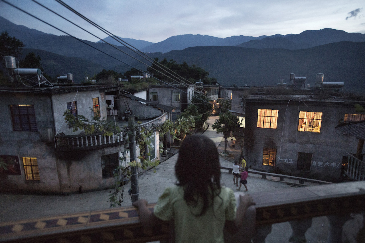 7-year-old Xiao Yuan looks at her village on a balcony at a neighbor's home in Yangxi village. Her mother gave birth to her at the age of 17. Xiao Yuan hasn't started school yet while the admission age is 6. Zhemi county, Yunnan province, China, October 27, 2014. © Muyi Xiao. All images courtesy of the Magnum Foundation.