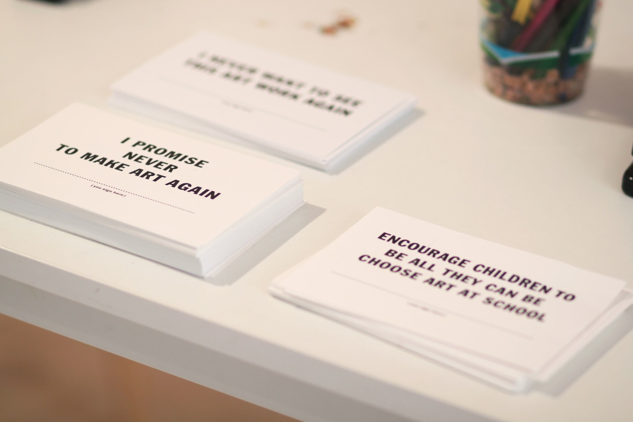 Artist pledge cards at the exhibition's front desk