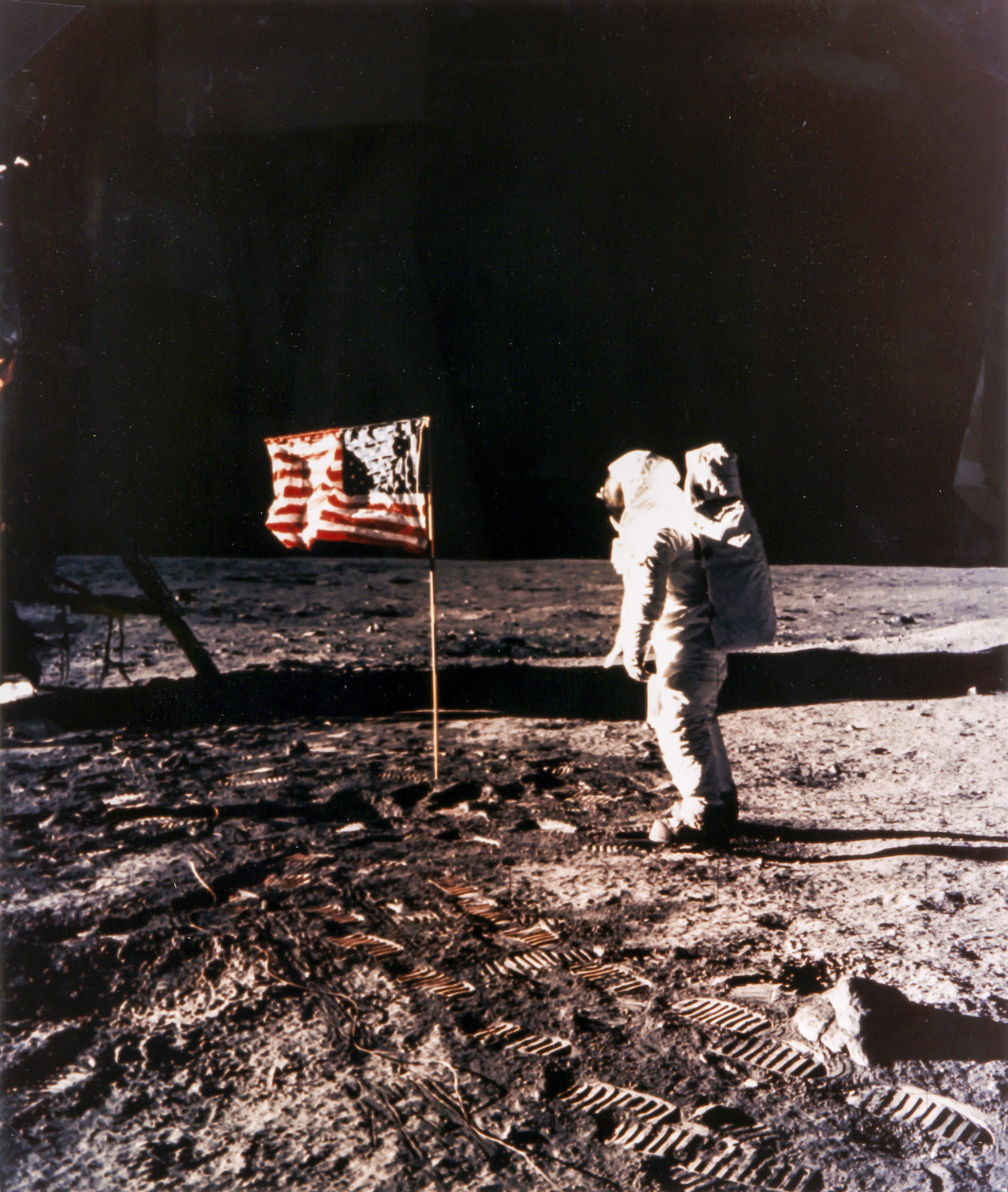 """Neil Armstrong Buzz Aldrin and the American flag on the Sea of Tranquillity, Apollo 11, July 1969 Large-format vintage chromogenic print on fibre-based Kodak paper, borderless, 60 x 51cm, """"A Kodak Paper"""" watermark on verso, NASA HQ caption on separate page, [NASA negative number AS11-40-5874] On the windless plain Aldrin saluted the American flag, stiffened with wire so it would """"wave"""". Illustrated: Moon p.194-195 Est. £5,000-7,000 Reproduction, © Bloomsbury Auctions"""