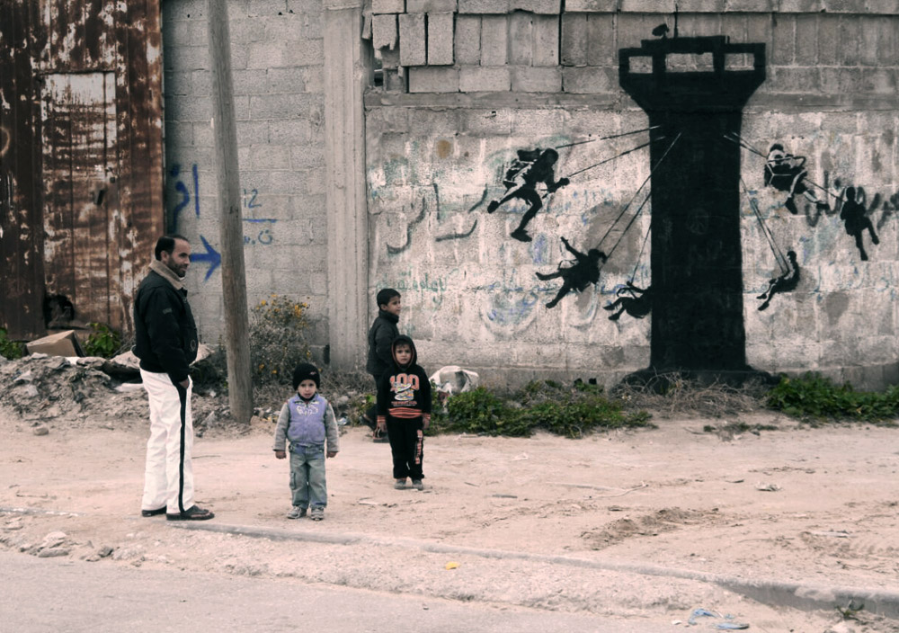 In this art work, children swing from an Israeli watch tower.