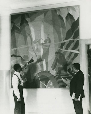"Artist Aaron Douglas (on the left) and Schomburg Collection curator Arthur A. Schomburg, examine Douglas's painting ""Aspects of Negro Life: Song of the Towers"" (1934) (via nypl.org)"