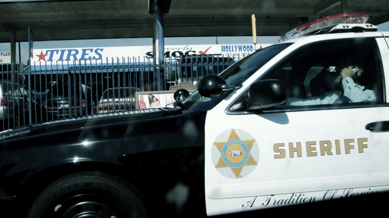 An LA County Sheriff's Department deputy talking on the phone while driving — which is illegal in California. (photo by Heather Anne Campbell/Flickr