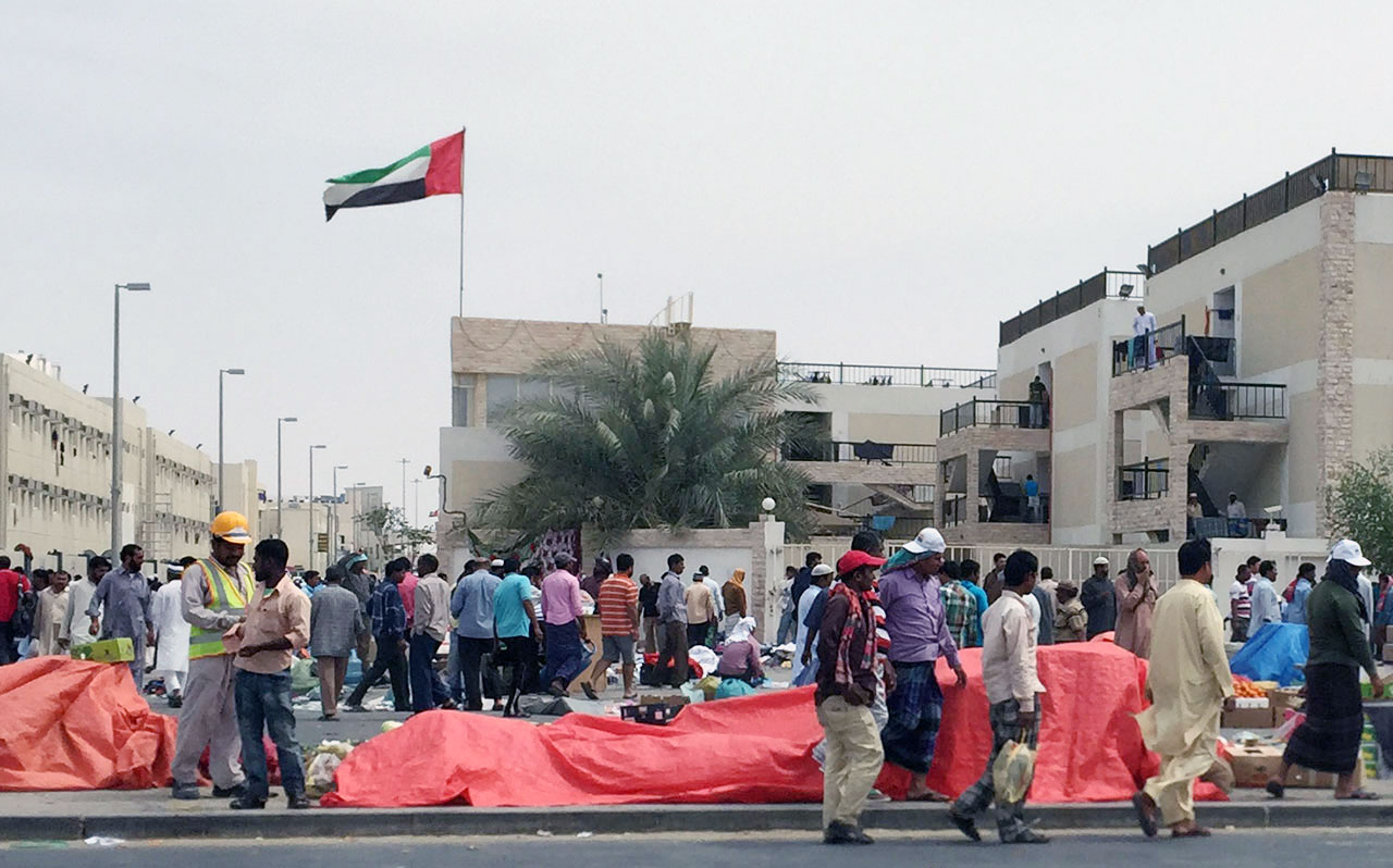 Migrant workers outside a workers' camp in Mafraq, Abu Dhabi. (photo by the author for Hyperallergic)