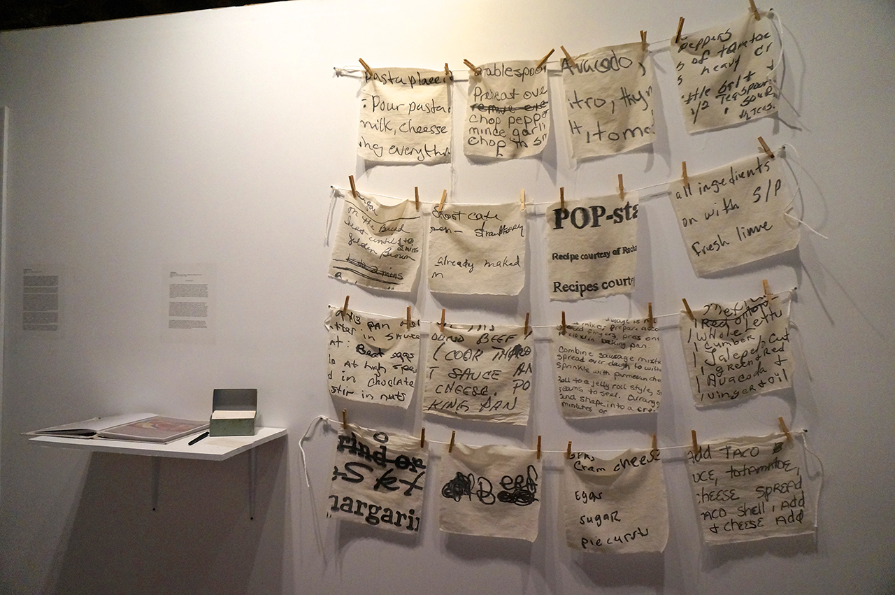 """Julia Rooney, """"THE RECIPE BOX"""" (2015), ink painted on cotton fabric, installed with clothespin and twine, 12"""" x 12"""" each"""