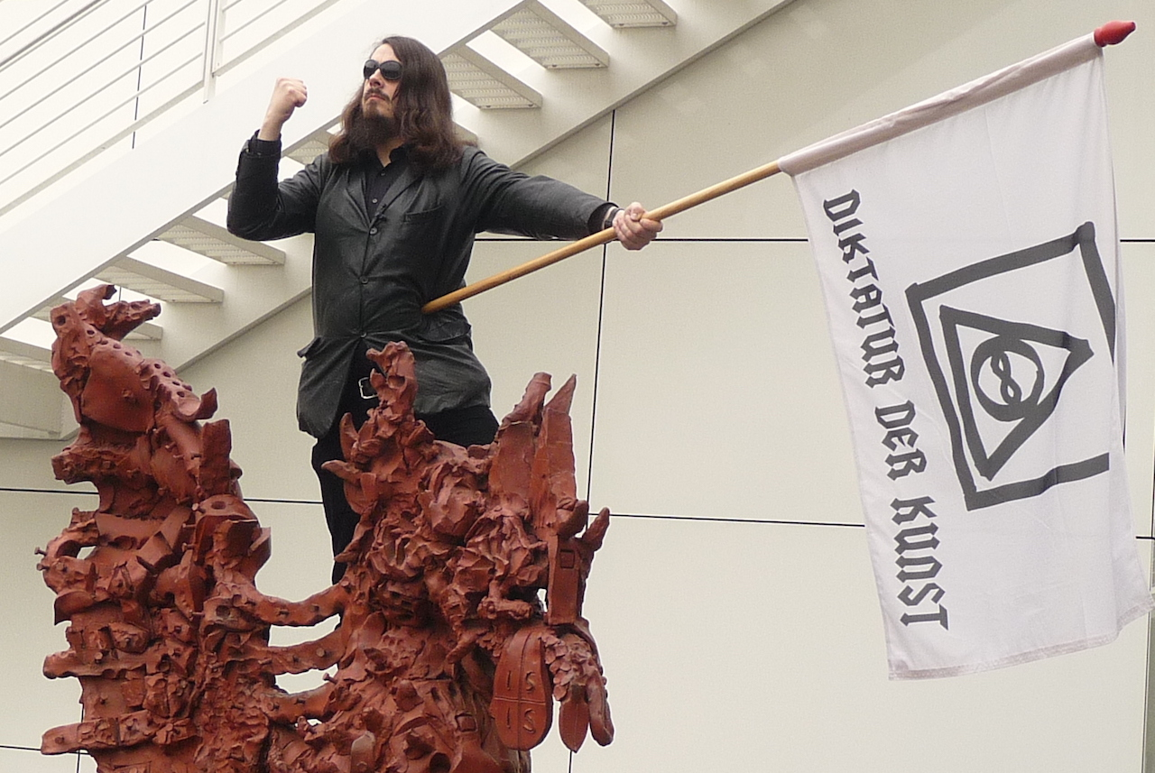 Jonathan Meese performing at the Arp Museum Bahnhof Rolandseck in 2009. (photo by Warburg, via Wikimedia Commons)