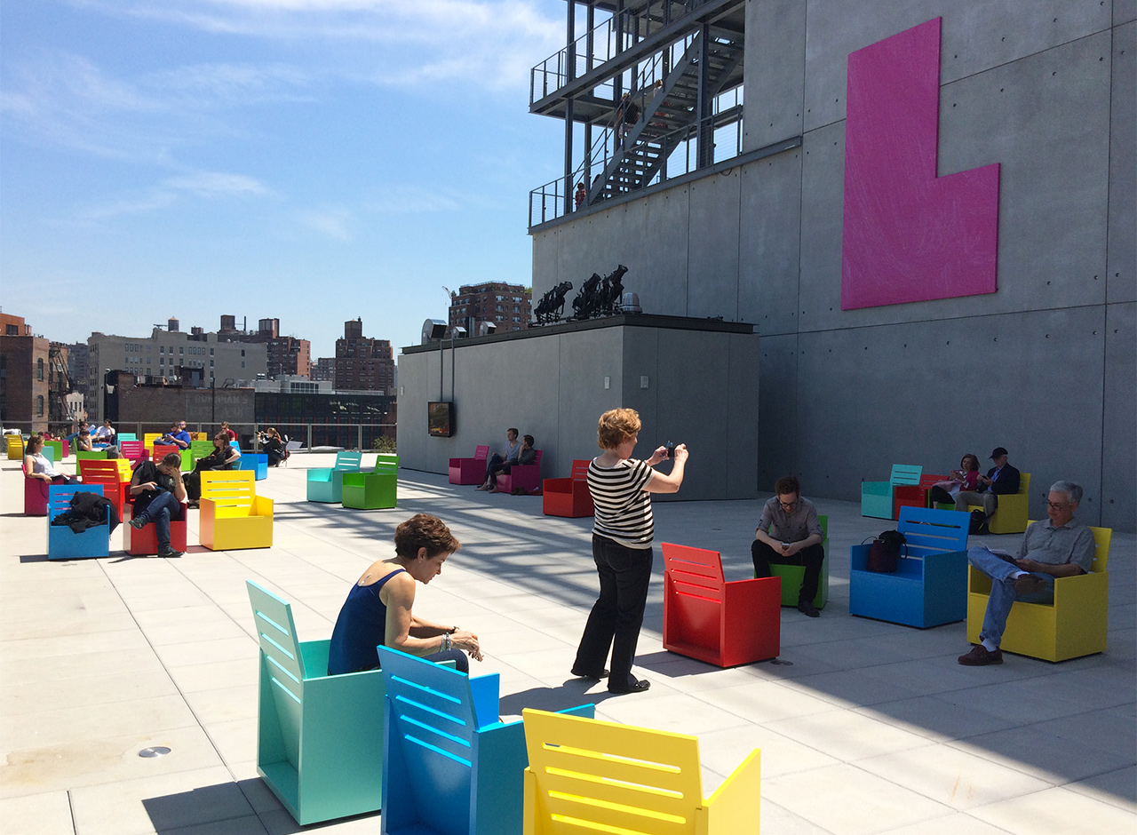 An outdoor terrace on the new Whitney Museum's fifth floor with chairs and a wall sculpture by Mary Heilmann