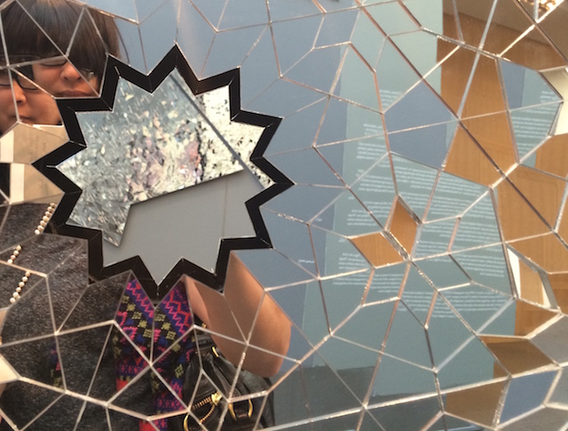 The layers of mirrors seem to encourage selfies, but the selfies appear in fractures and refractions.