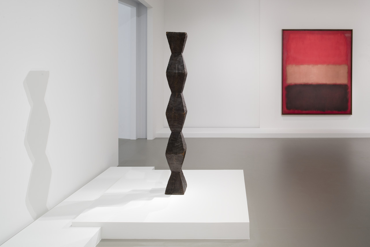 """Installation view of Constantin Brancusi's """"Endless Column, Version 1"""" (1918) and Mark Rothko's """"No. 46 [Black, Ochre, Red over Red]"""" (1957)"""
