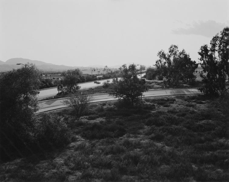 "Robert Adams, ""Looking toward Los Angeles, Interstate 10, west edge of Redlands, California"" (1982), Gelatin silver print, Image: 9 x 11 1/4 inches (via matthewmarks.com)"