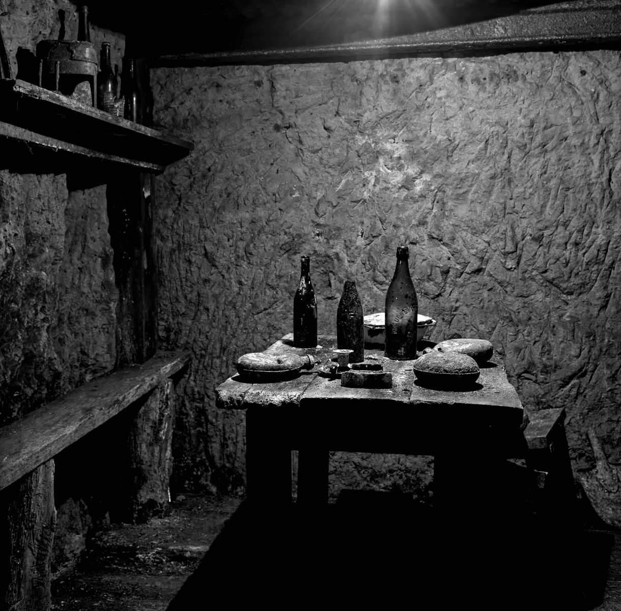 French soldiers' dining area underground with wine bottles, canteens and a serving dish. Photographed 6 December 2011. Vauquois, France. Terms of Use: These photos are for one-time use before January 1, 2015, limited to professional media outlets and blogs, in connection with an accompanying story about Jeffrey Gusky, his work and WWI-related discoveries. Stories appearing during the license period may be archived online by the media outlet or blog who published the story. This image is a low resolution version of the original. Higher resolution images are available by special arrangement with the artist. This image may not be modified and may not be used commercially except with a commercial license. This image is not available under any Creative Commons license. Copyright (c) 2011, Jeffrey Gusky. All Rights Reserved. Jeffrey Gusky, c/o attorney at P.O. Box 2526, Addison, TX 75001-2526. photos@jeffgusky.com .