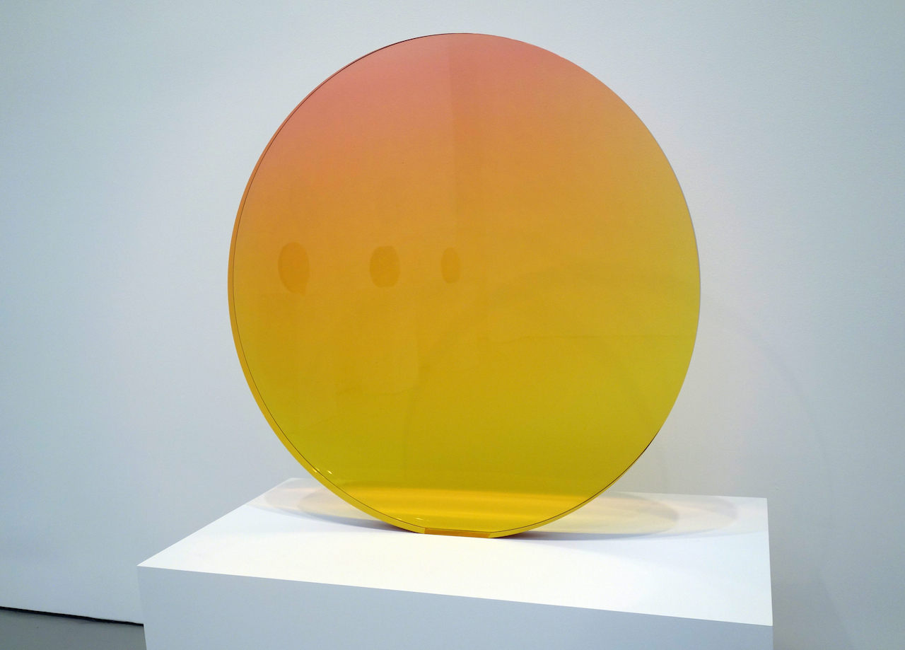 """De Wain Valentine, """"Circle Amber-Rose"""" (1970), cast polyester resin, 33 5/8 x 33 3/4 x 2 inches"""