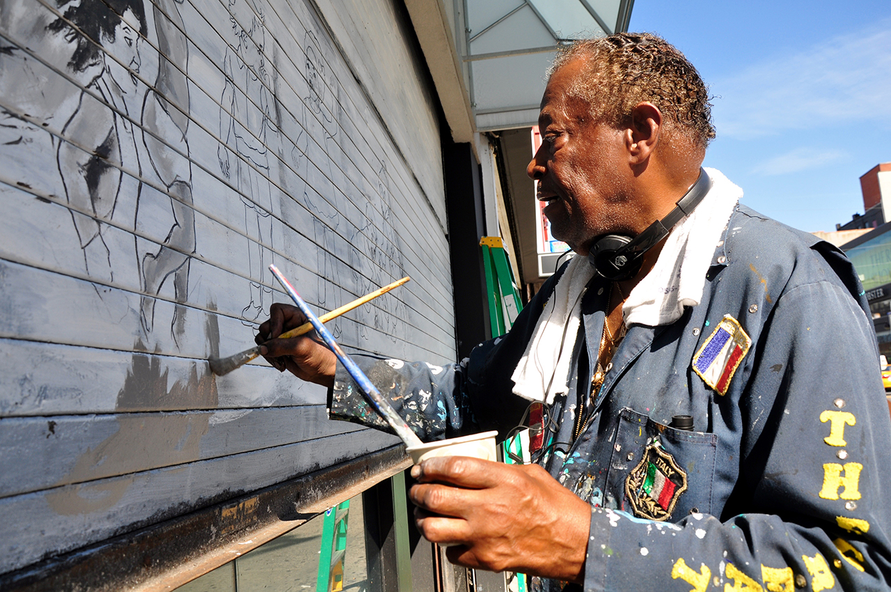 The Picasso of Harlem at work on the Children's Place mural (click to enlarge)