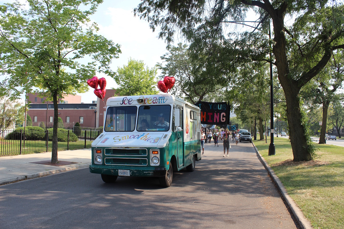An ice cream truck leads the procession, giving out free ice cream to community members the procession passe