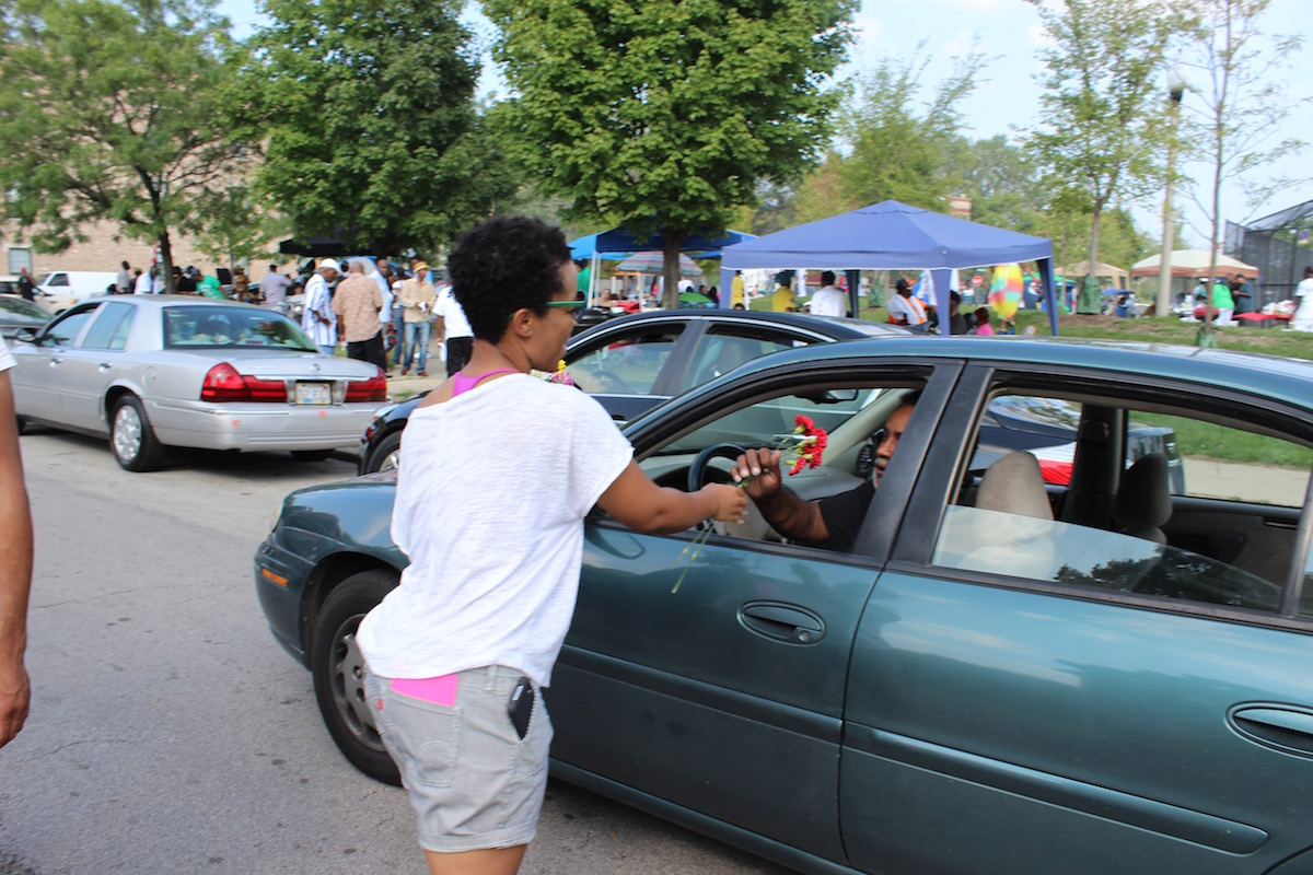 Tempestt Hazel, curator, writer, and artist advocate, hands out flowers to a passing community member in Bronzeville during the Black Love Procession on September 6, 2015 (click to enlarge)