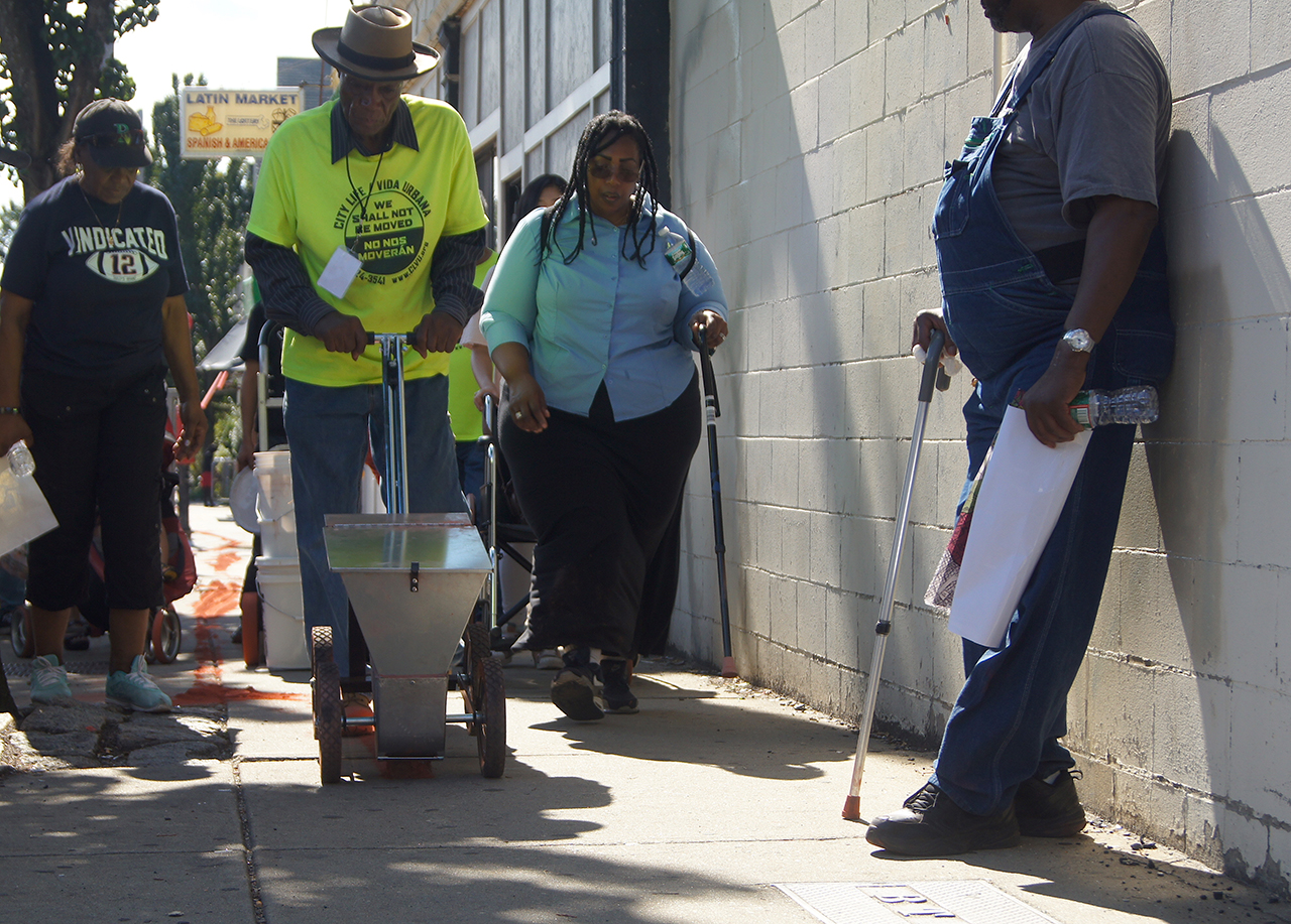 Heather Gordon, Mr. Marshal, and Carolyn Lomax push the chalker tool along Washington Corridor.