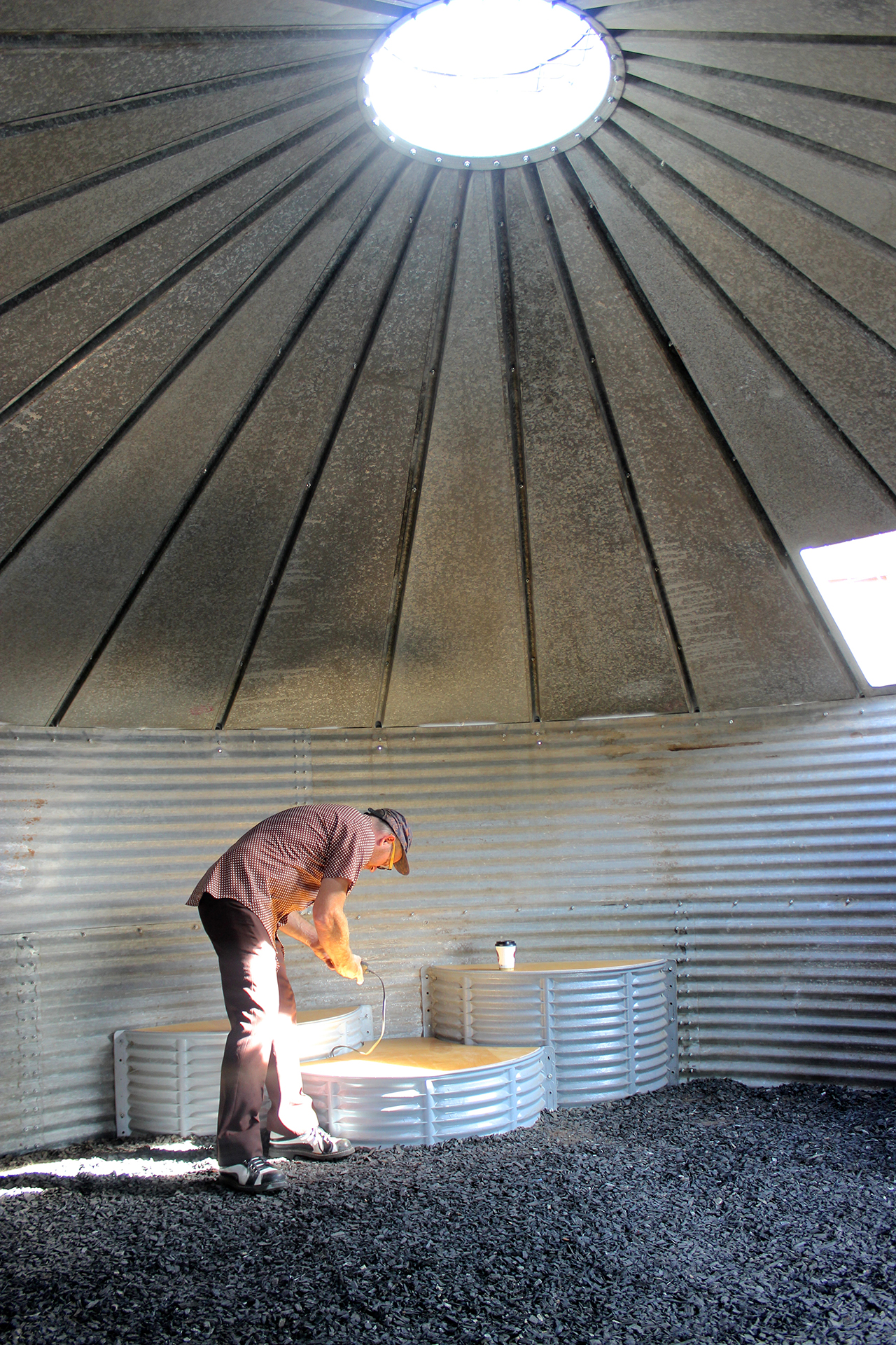Jon Brumit plugs his phone in to activate the sound silo. Visitors can sub their own music players and experience them through the filter of the house. (click to enlarge)