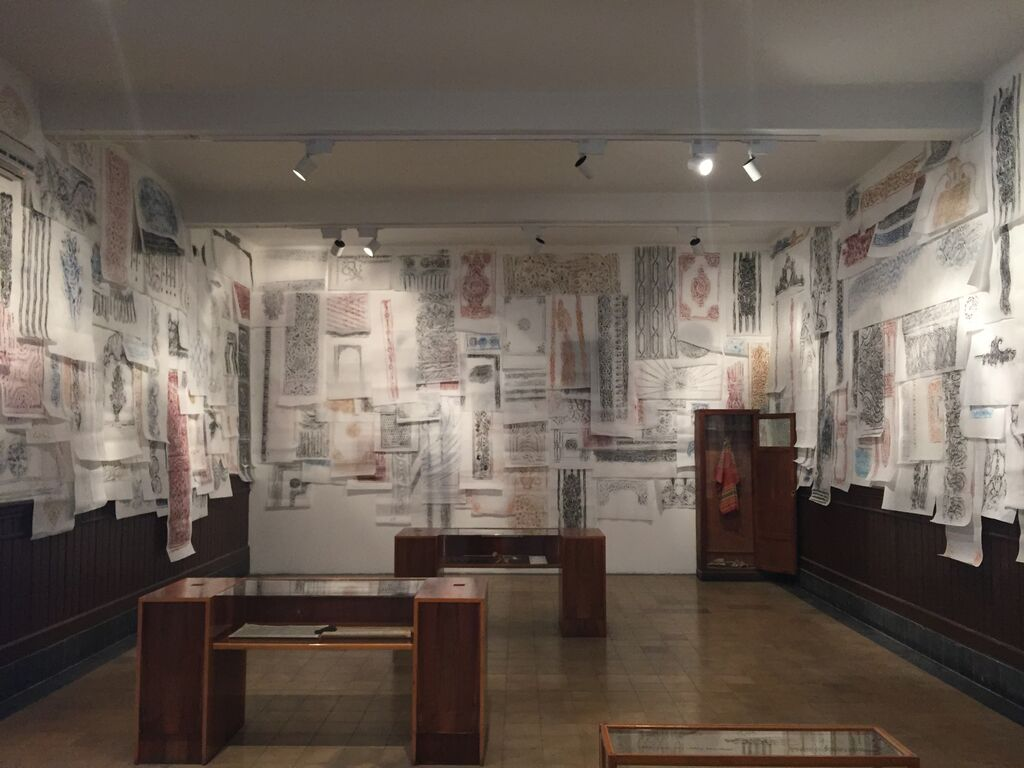 """Hallway with glass-and-wood cases and architectural rubbings in Michael Rakowitz, """"The Flesh is Yours, The Bones are Ours"""" at Galata Greek Primary School (click to enlarge)"""
