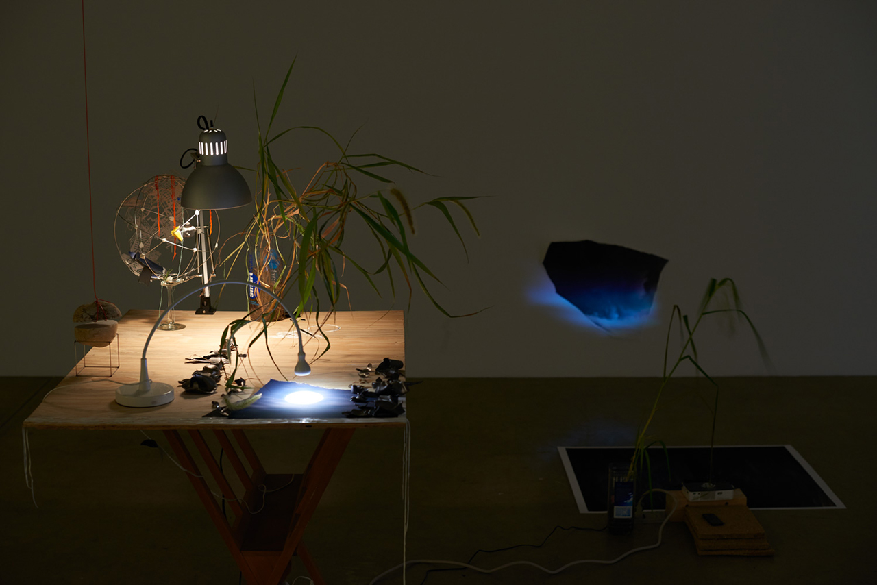 """Sarah Sze, """"Seconds Clipped"""" (2015), wood, video projectors, lamps, stone, glazed ceramic, plants, archival prints, glass, 180 x 93 x 90 in (457.2 x 236.2 x 228.6 cm) (photo by Brett Moen, courtesy the artist and Tanya Bonakdar Gallery, New York)"""