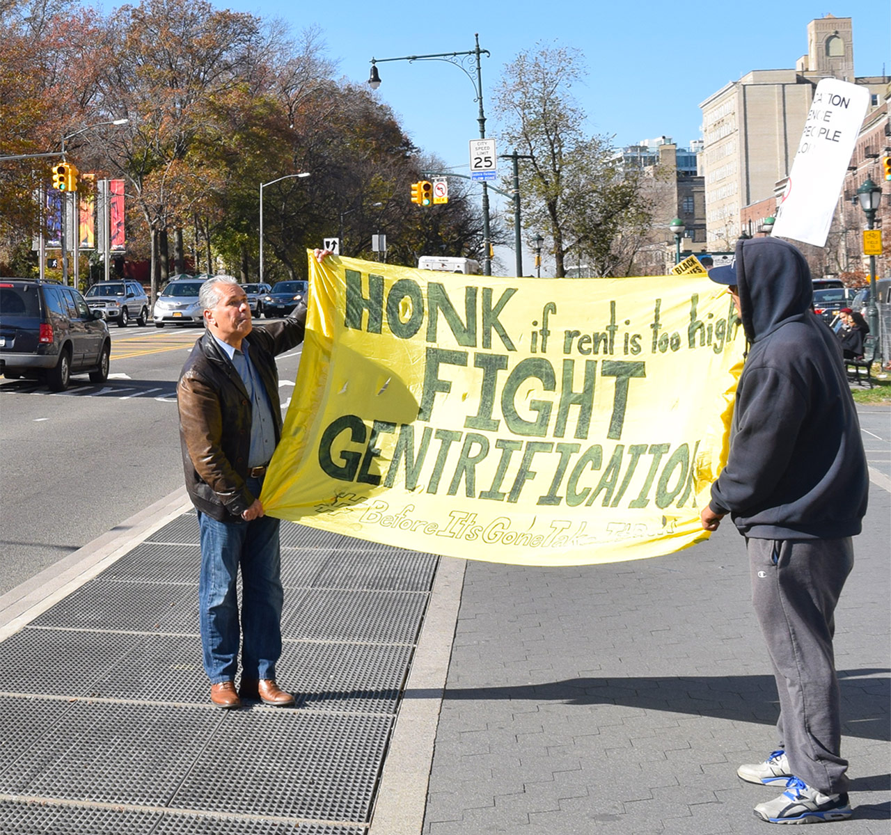 Anti-gentrification protesters hold up a sign on Eastern Parkway during a recent protest at the Brooklyn Museum.
